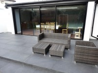 rattan sofa on black porcelain tile patio